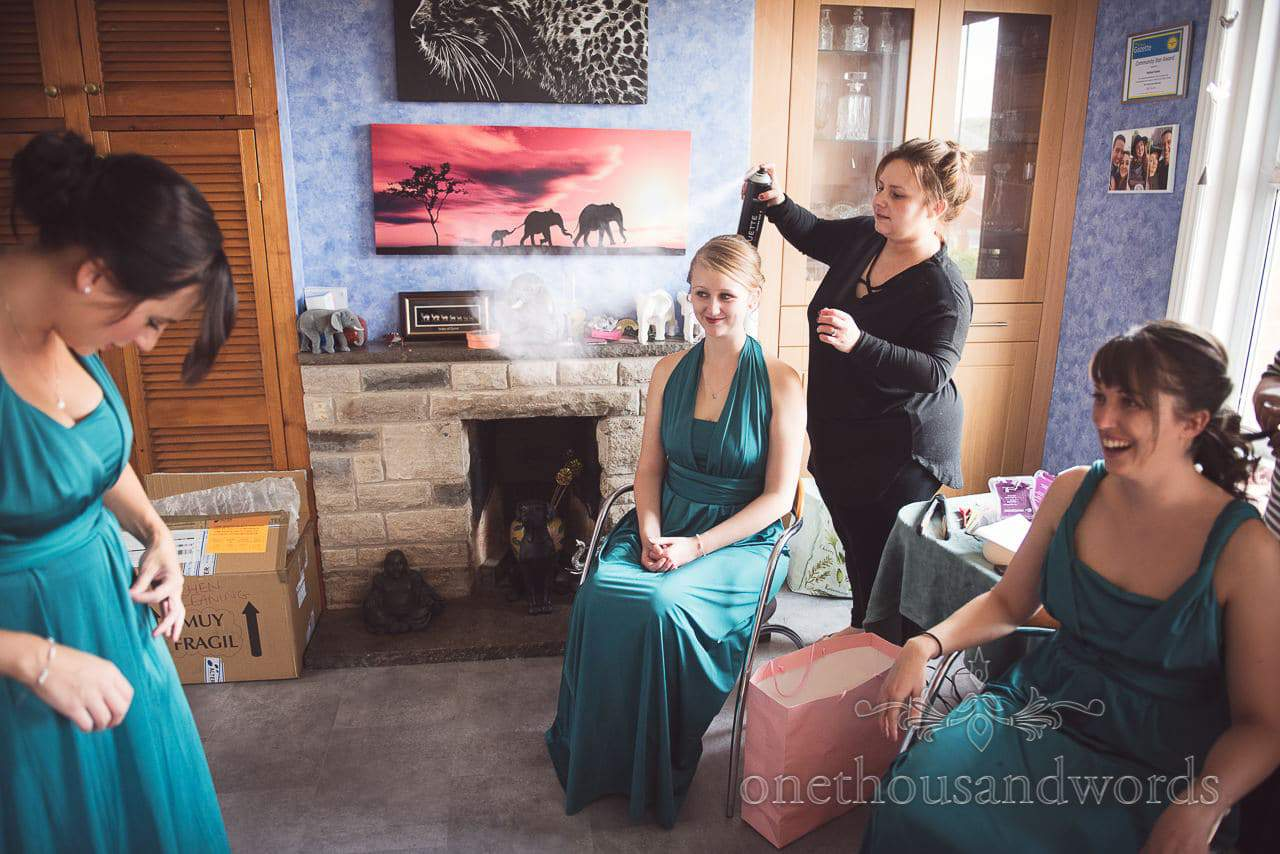 Bridesmaids in teal colour dresses have hair styled before Lulworth Castle Wedding Photographs