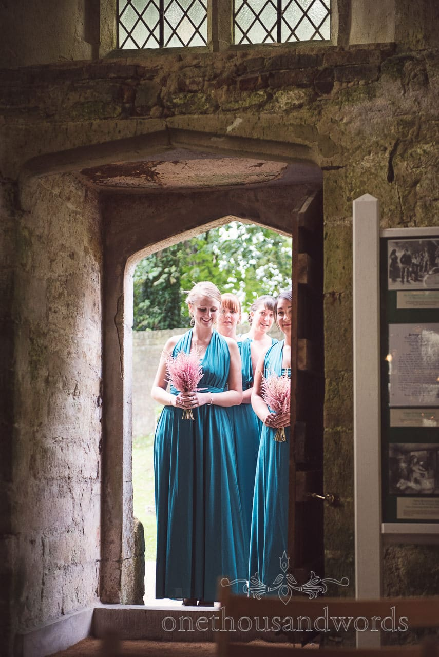 Bridesmaids wait in church doorway at Lulworth Castle Wedding Photographs