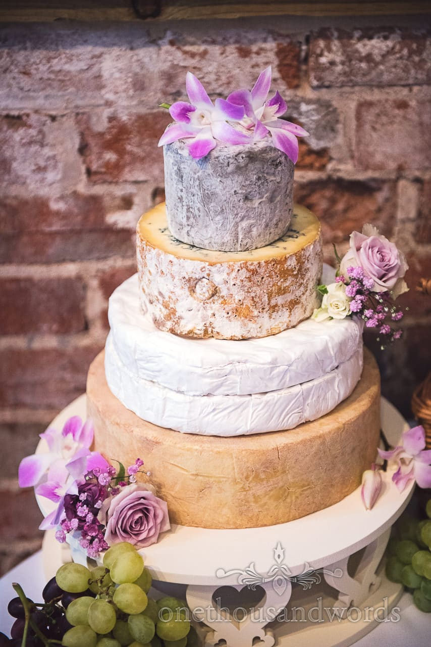 Cheese wedding cake in front of red brick wall at Highcliffe Castle Wedding