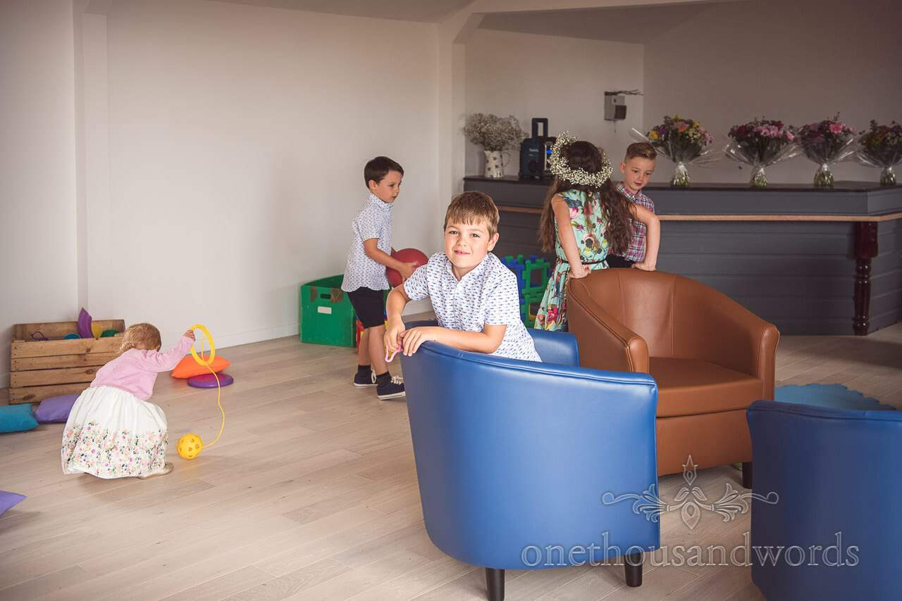 Child wedding guest play in play room at home wedding in Dorset