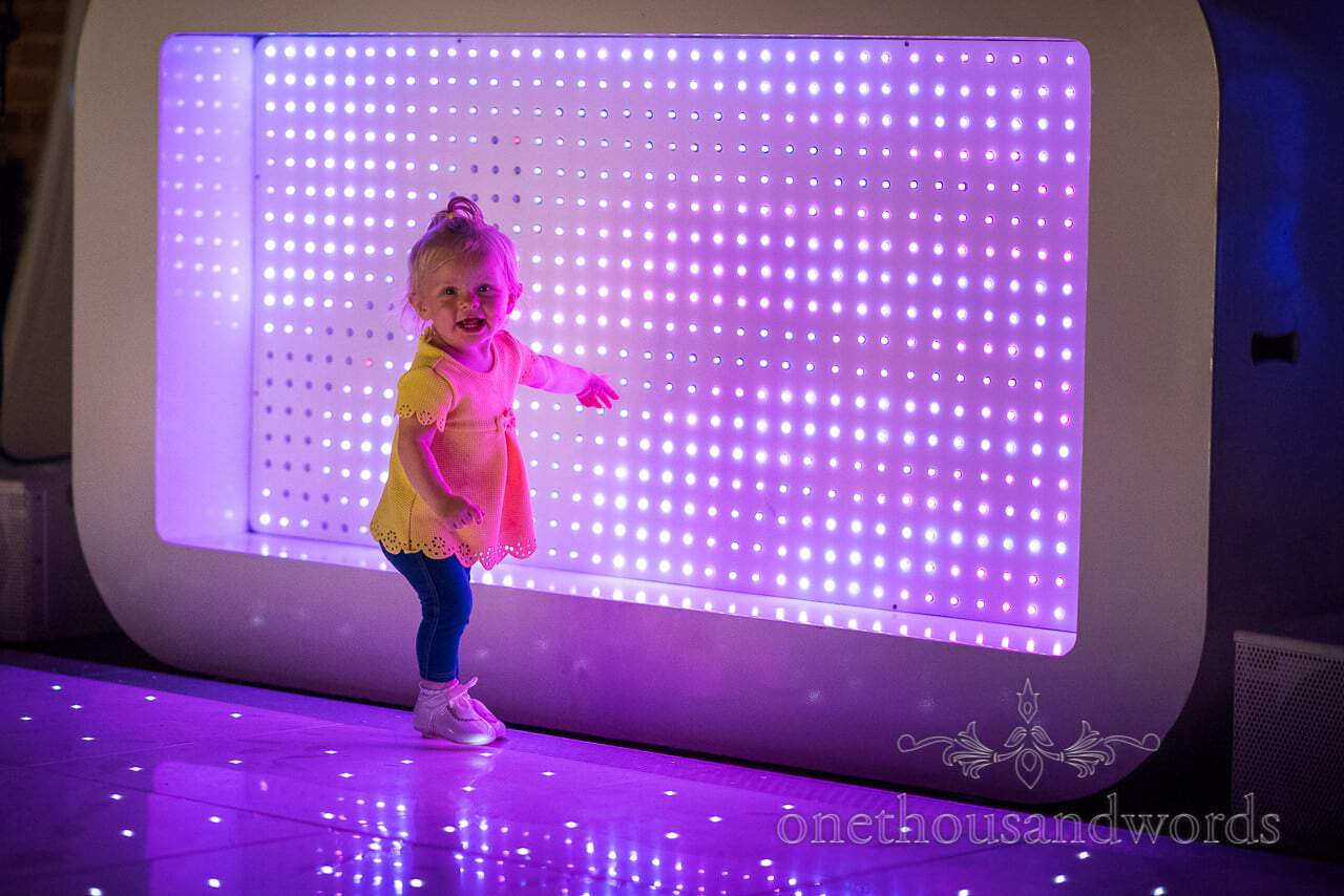 Child wedding guest plays with wedding DJ's LED display at Highcliffe Castle Wedding