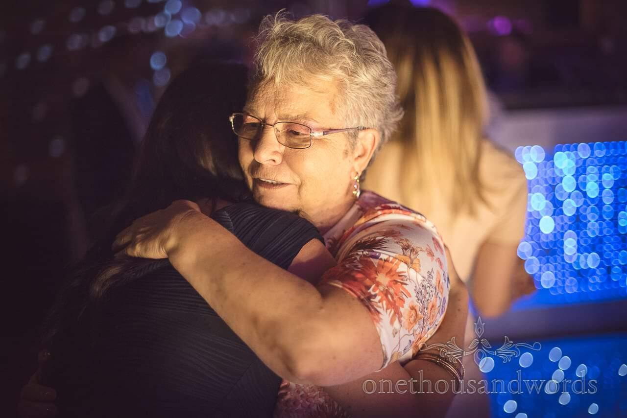Elderly wedding guest hugging on dance floor at Highcliffe Castle Wedding