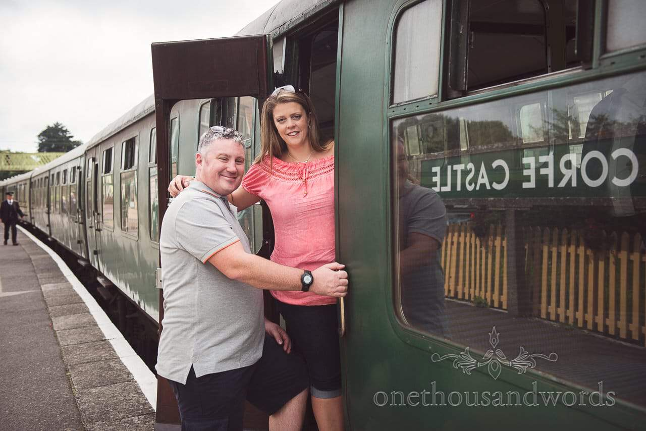 Engaged couple board steam train carriage at Corfe Castle steam railway station