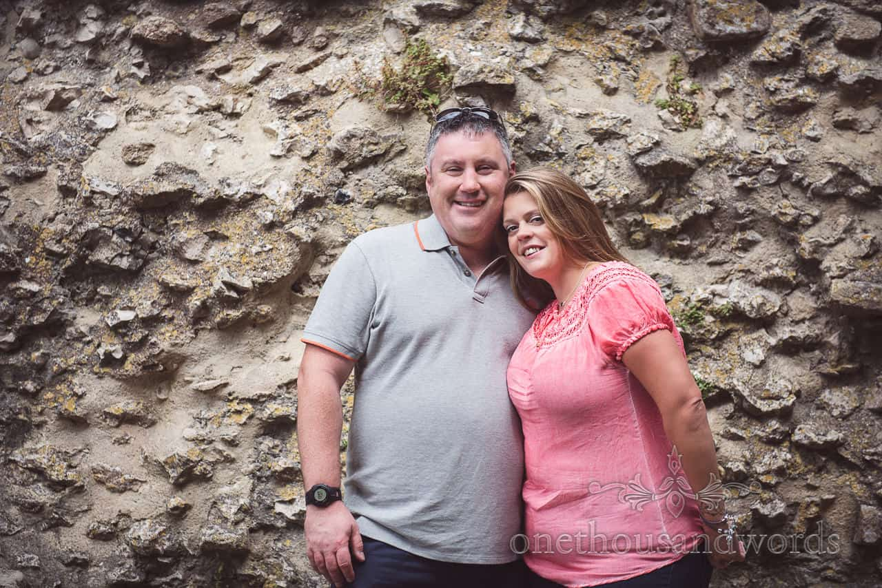 Engaged couple pose in front of ruined stone castle wall at Corfe Castle in Dorset