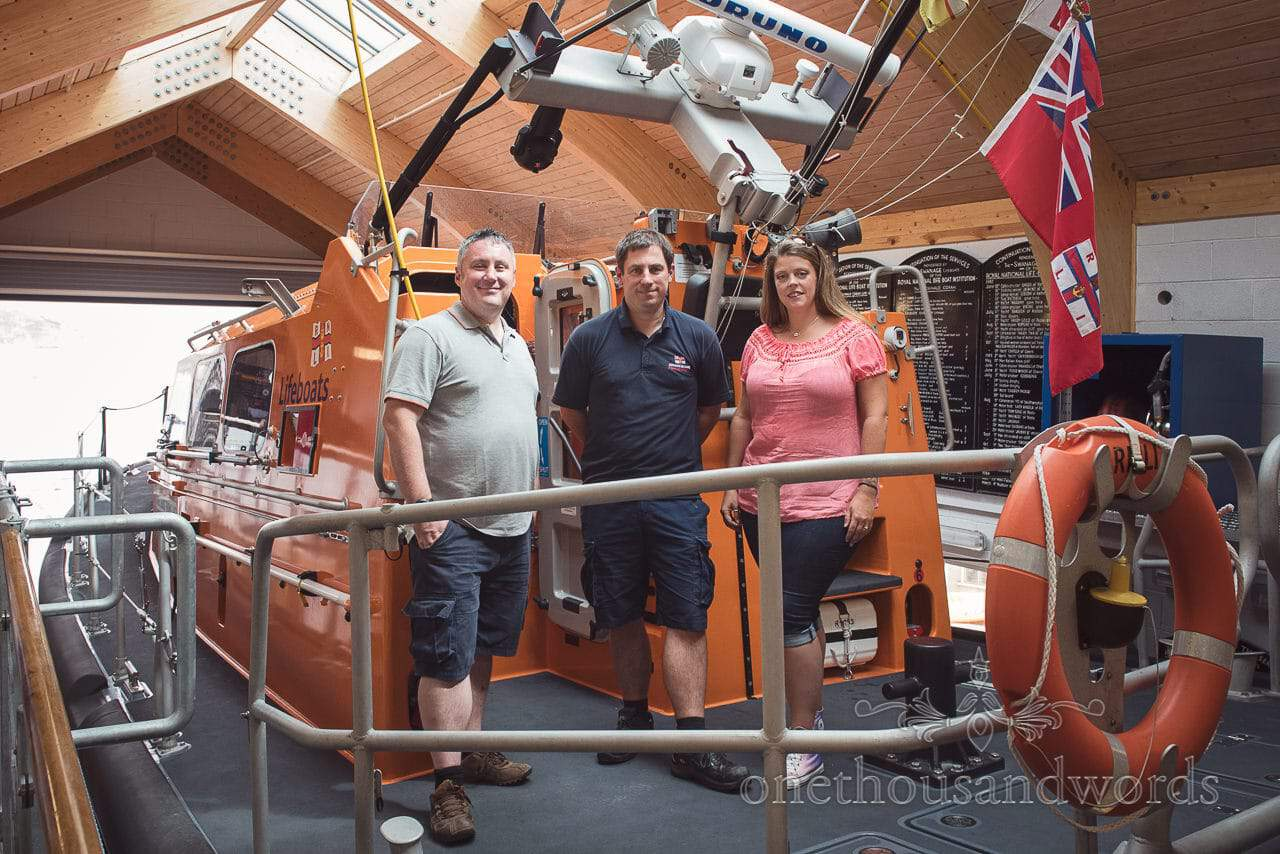 Engaged couple pose with Swanage Lifeboat crewman on lifeboat