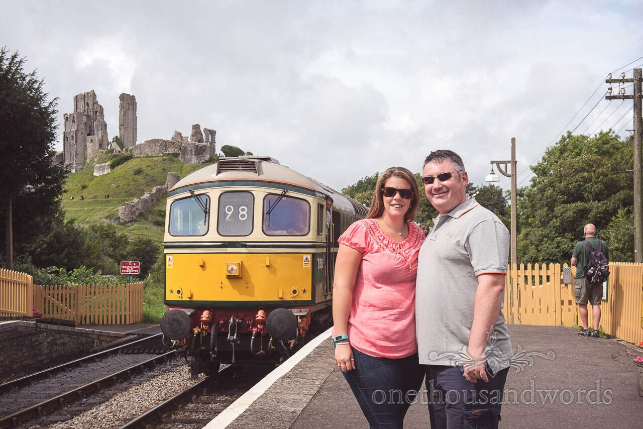Engagement photo shoot with train and ruined castle at Corfe Castle steam railway station