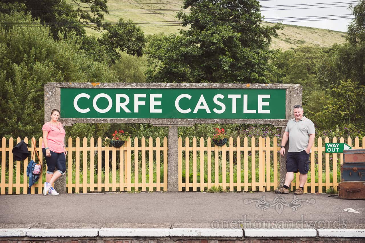Engagement Photograph of bride and groom to be with Corfe Castle railway sign