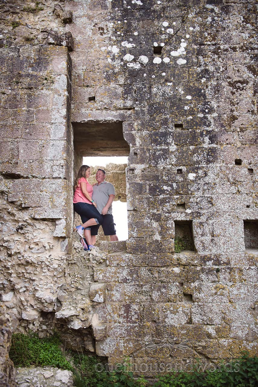 Engagement Photograph of couple in window of Corfe Castle Dorset wedding venue