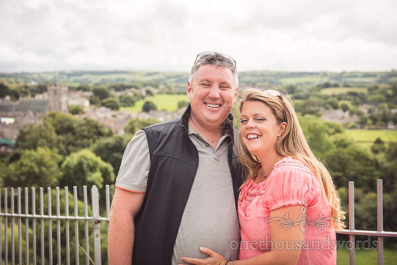 Engagement Photograph of couple laughing with view from Corfe Castle in Dorset