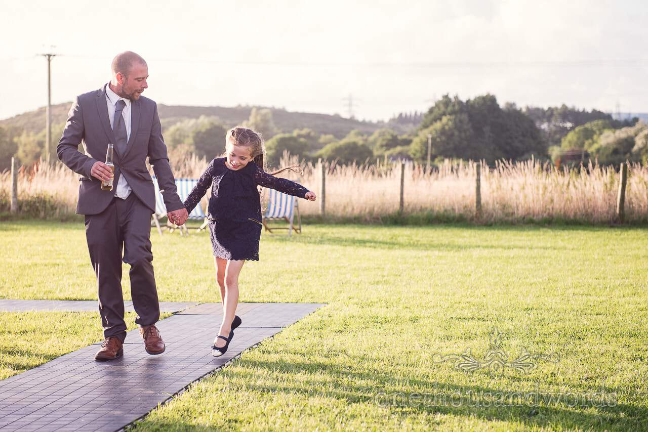 Father and skipping daughter at evening wedding reception