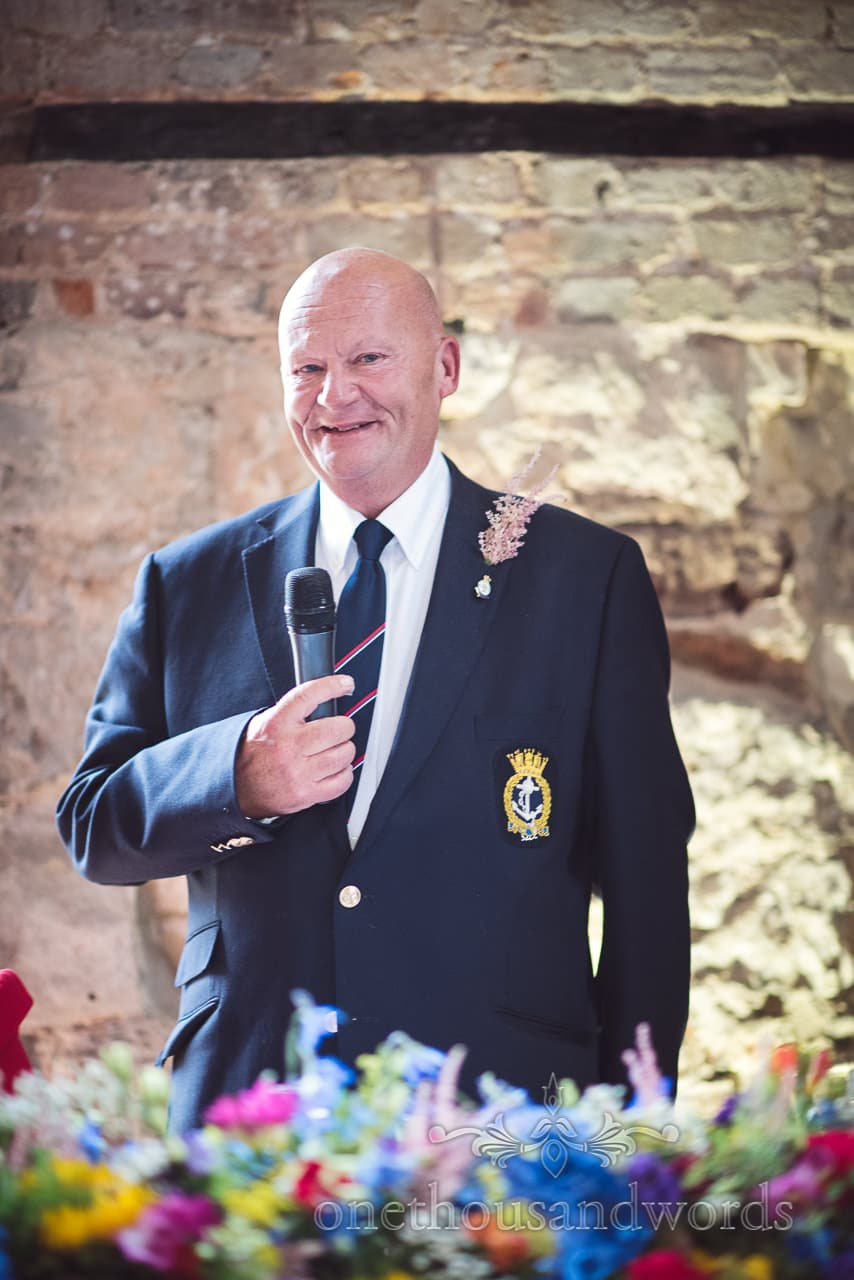 Father of the bride in navy suit makes wedding speech at Lulworth Castle Wedding