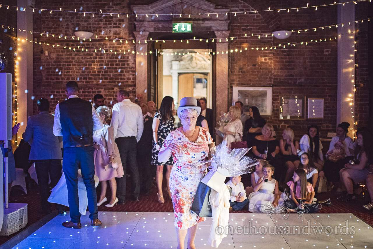 Female wedding guest with top hat walks on dance floor at Highcliffe Castle Wedding