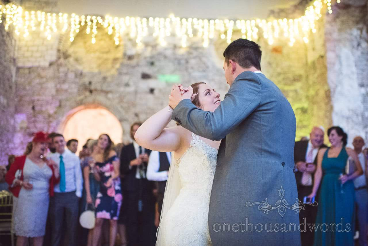 First dance under fairy lights watched by guests at Lulworth Castle Wedding
