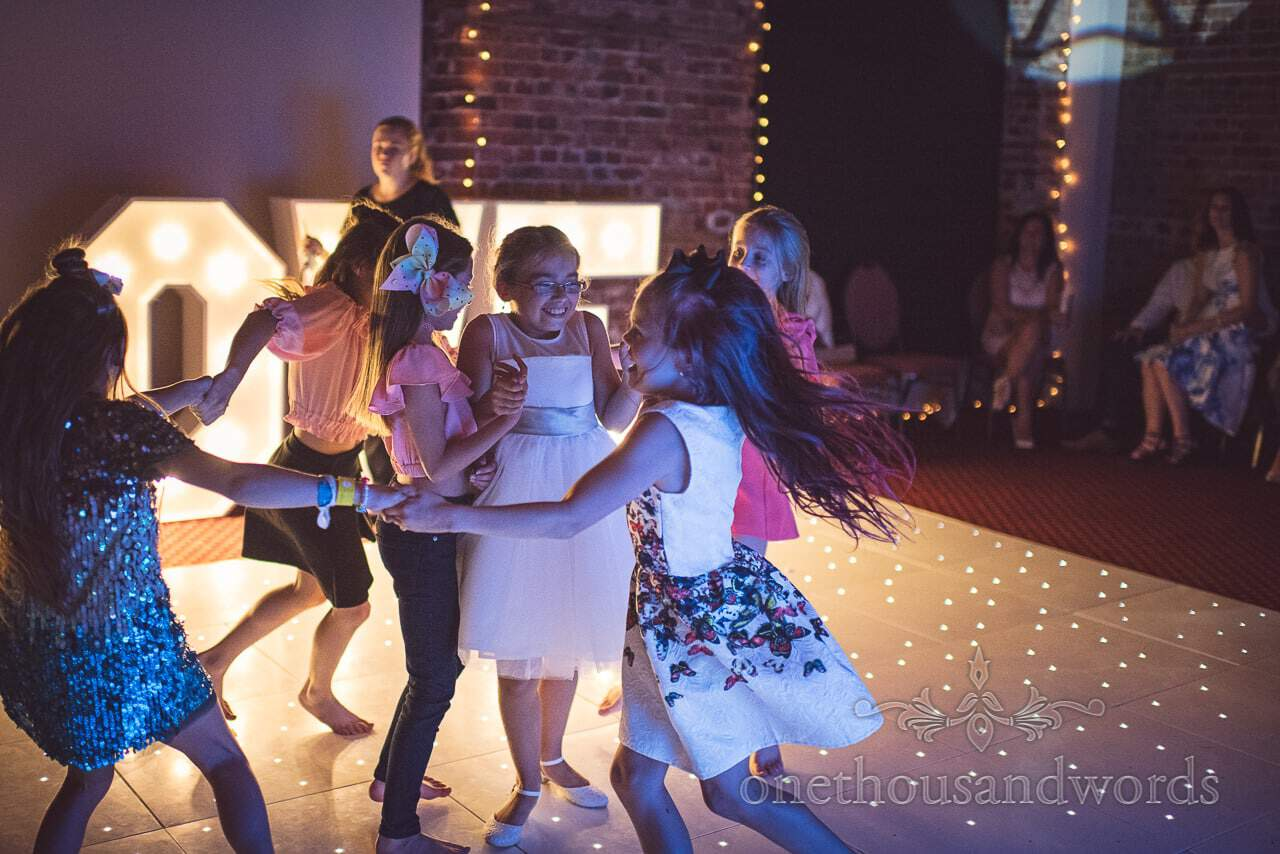 Flower girl and friends dance in circle on dance floor at Highcliffe Castle Wedding