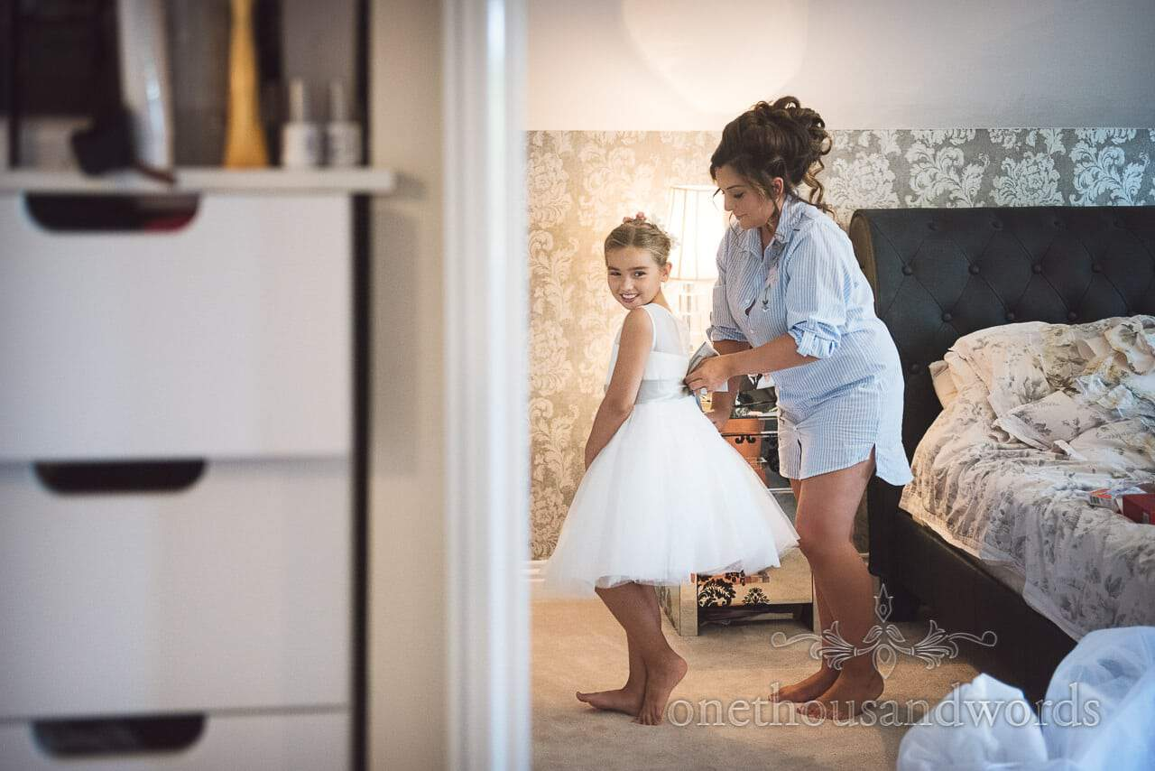 Flower girl is laced into her white dress by bride on wedding morning in Dorset