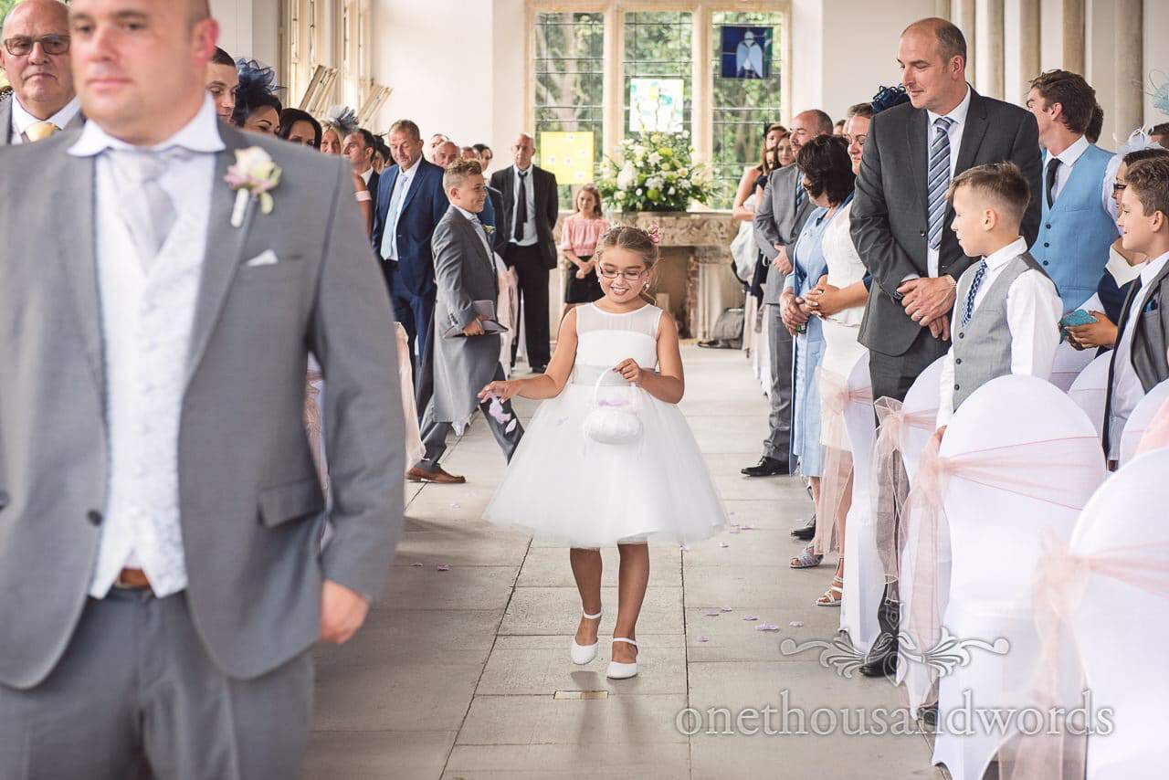 Flower girl sprinkles petals down the aisle at Highcliffe Castle Wedding Photographs