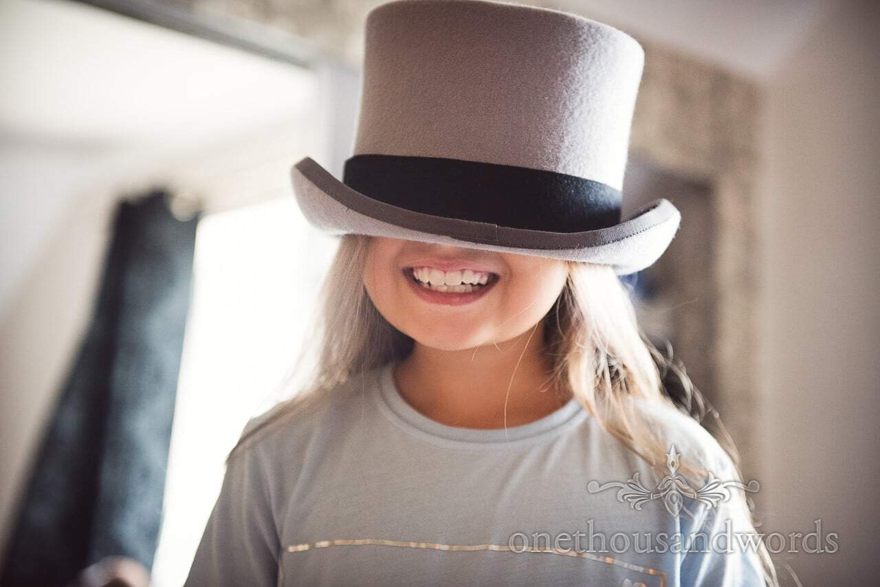 Flower girl wears grey top hat with black band that is too big for her head