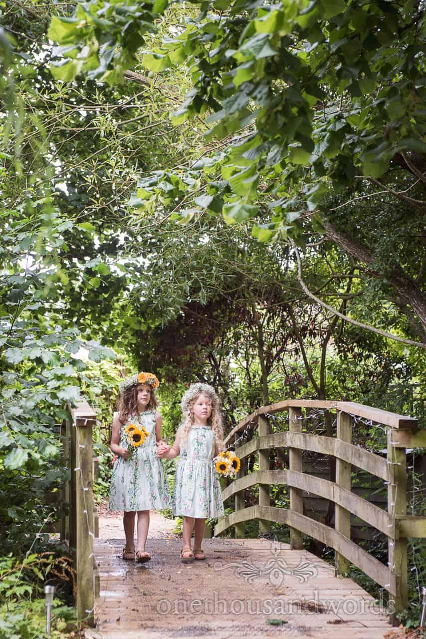 Flower girls with sunflower bouquets walk over bridge at Morten Walled Gardens Wedding