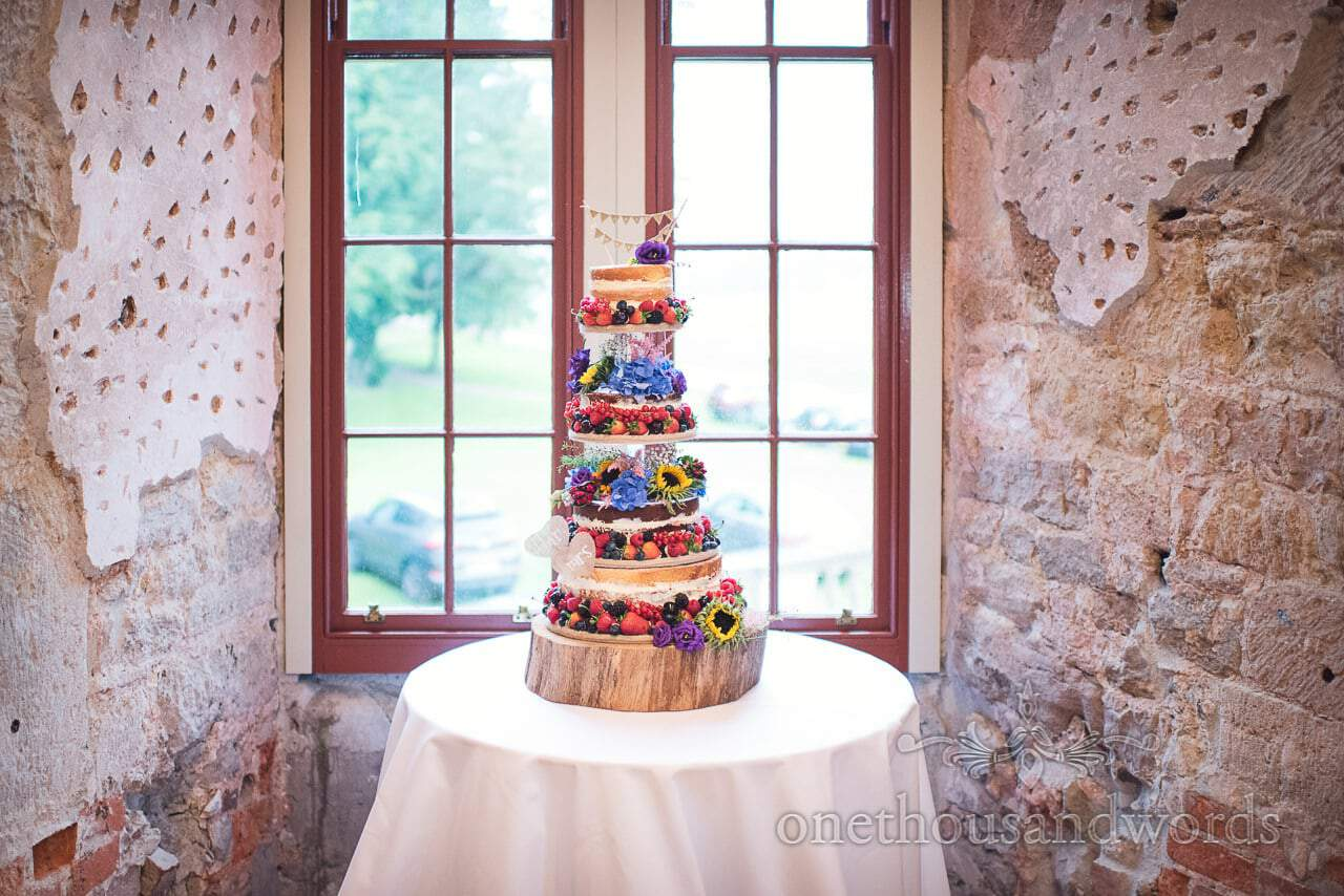 Four tier wedding cake with fruit and flowers at Lulworth Castle Wedding