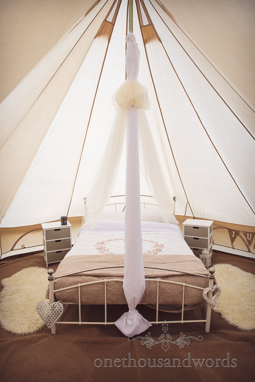 Glamping bed, sheep skin rugs and furniture in wedding bell tent for wedding night