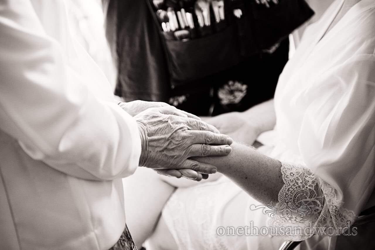 Grandmother holds brides hand on morning of Lulworth Castle Wedding Photographs