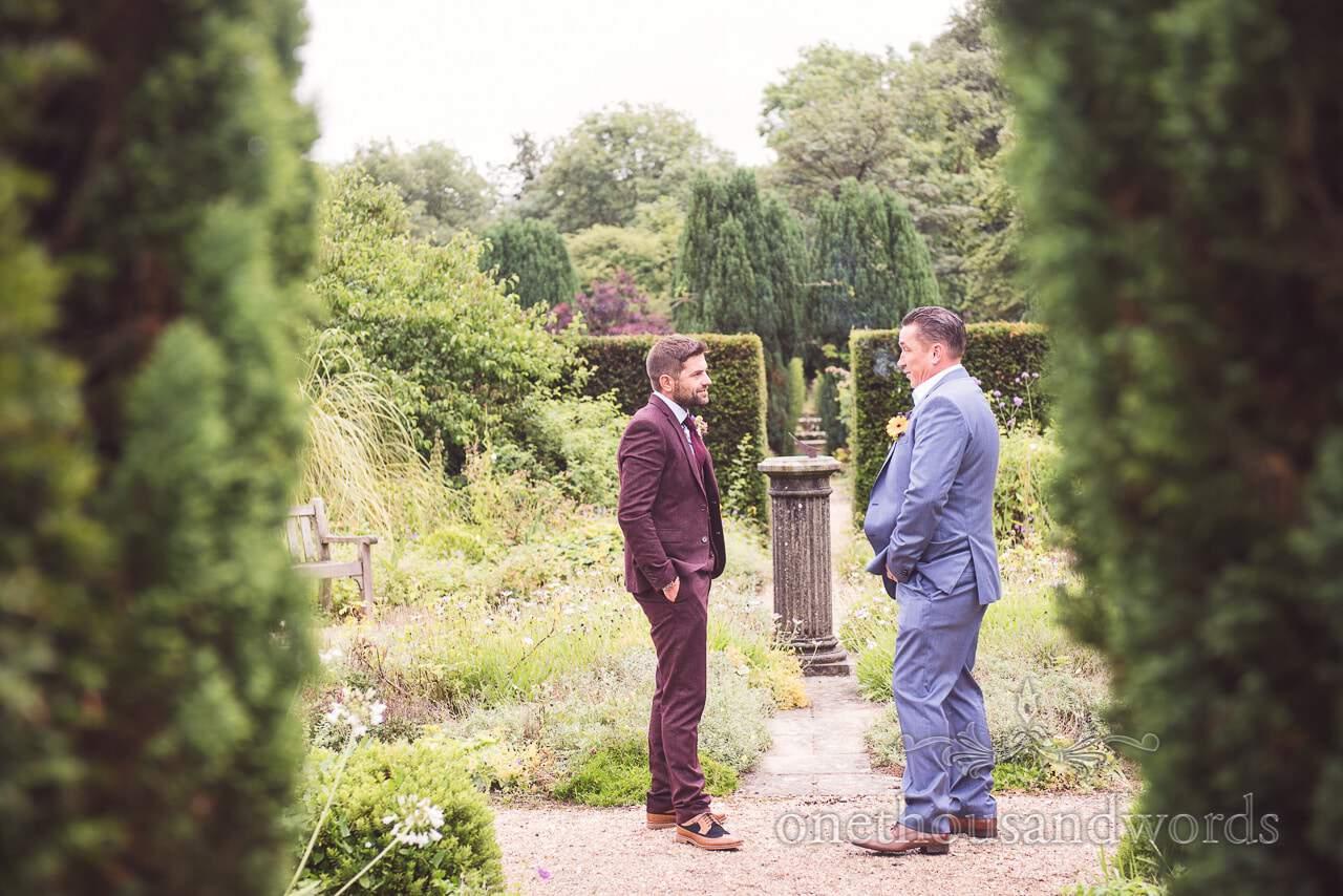 Groom and best man relax in gardens before Morten Walled Gardens Wedding