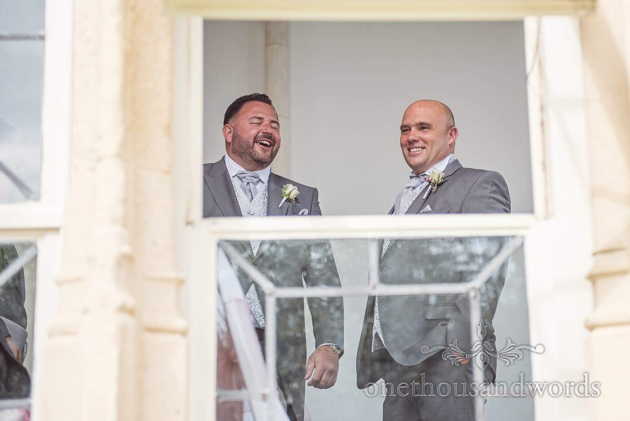 Groom and best men laughing through window at Highcliffe Castle Wedding venue