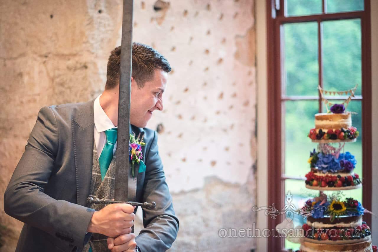 Groom attacks wedding cake with large sword at Lulworth Castle Wedding