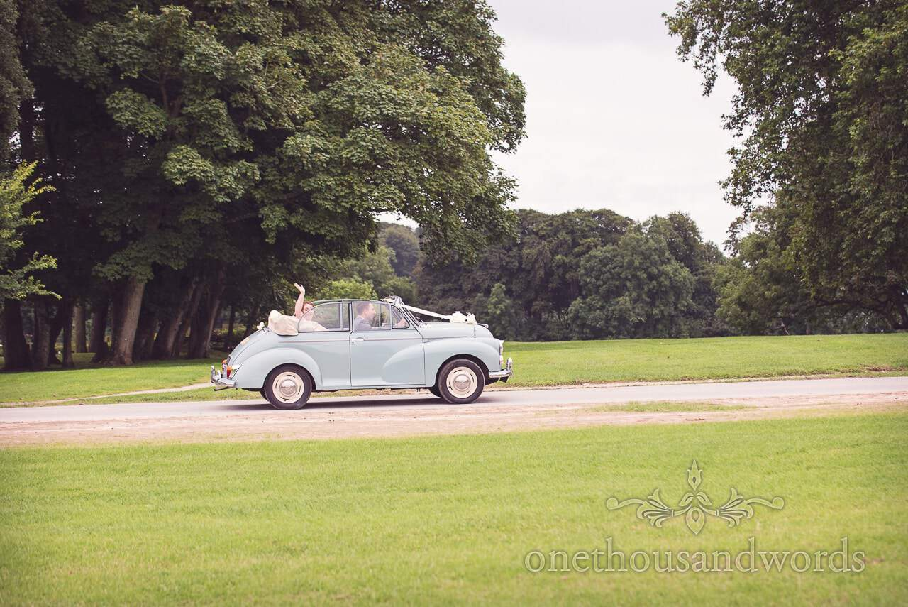 Groom drives the bride in classic Morris wedding car at Lulworth Castle Wedding Photographs