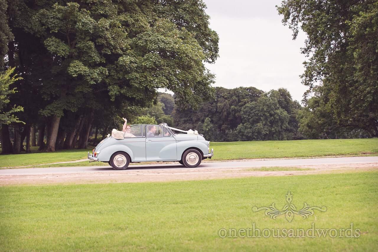 Groom drives the bride in classic Morris wedding car at Lulworth Castle Wedding Photographs