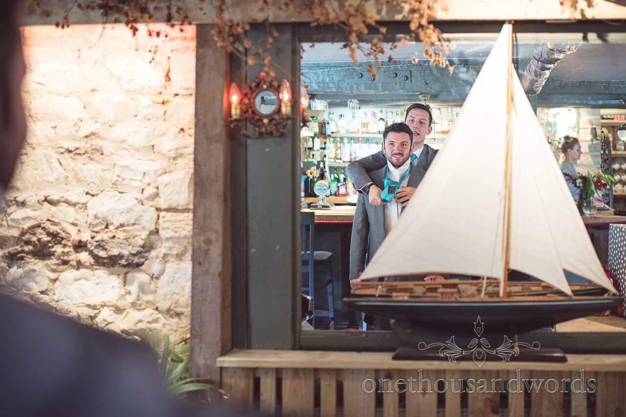 Groom helping Groomsmen with wedding tie in pub mirror