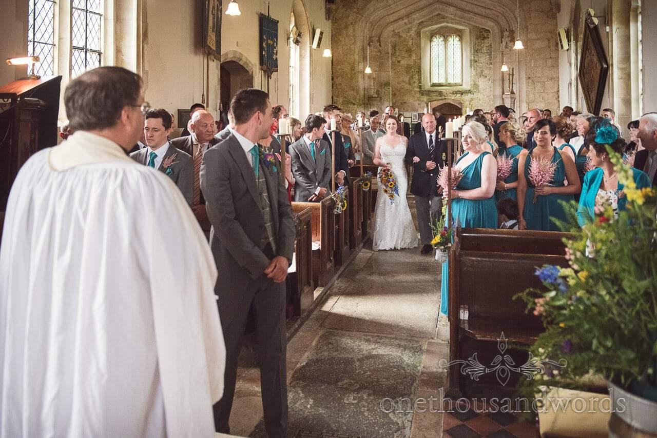 Groom looks at bride as she arrives at Lulworth Castle Wedding Photographs