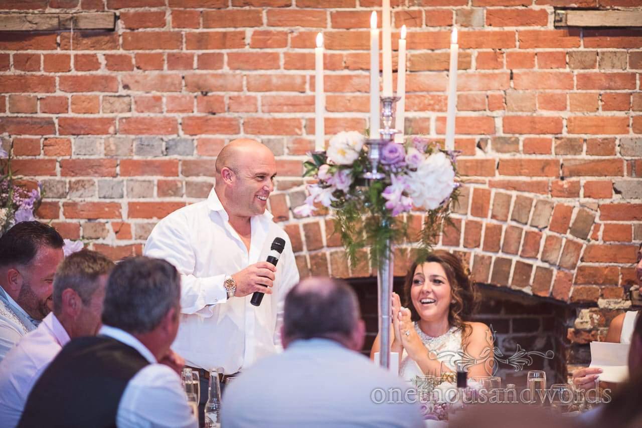 Groom makes wedding speech as bride claps at Highcliffe Castle Wedding