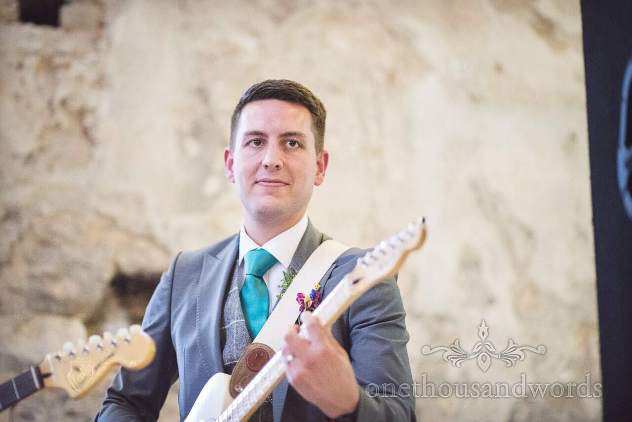 Groom plays guitar at his own wedding with wedding band at Lulworth Castle Wedding