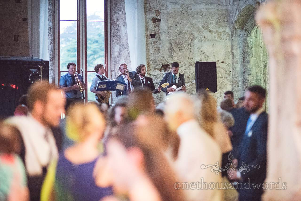 Groom plays guitar with wedding band at Lulworth Castle Wedding evening reception