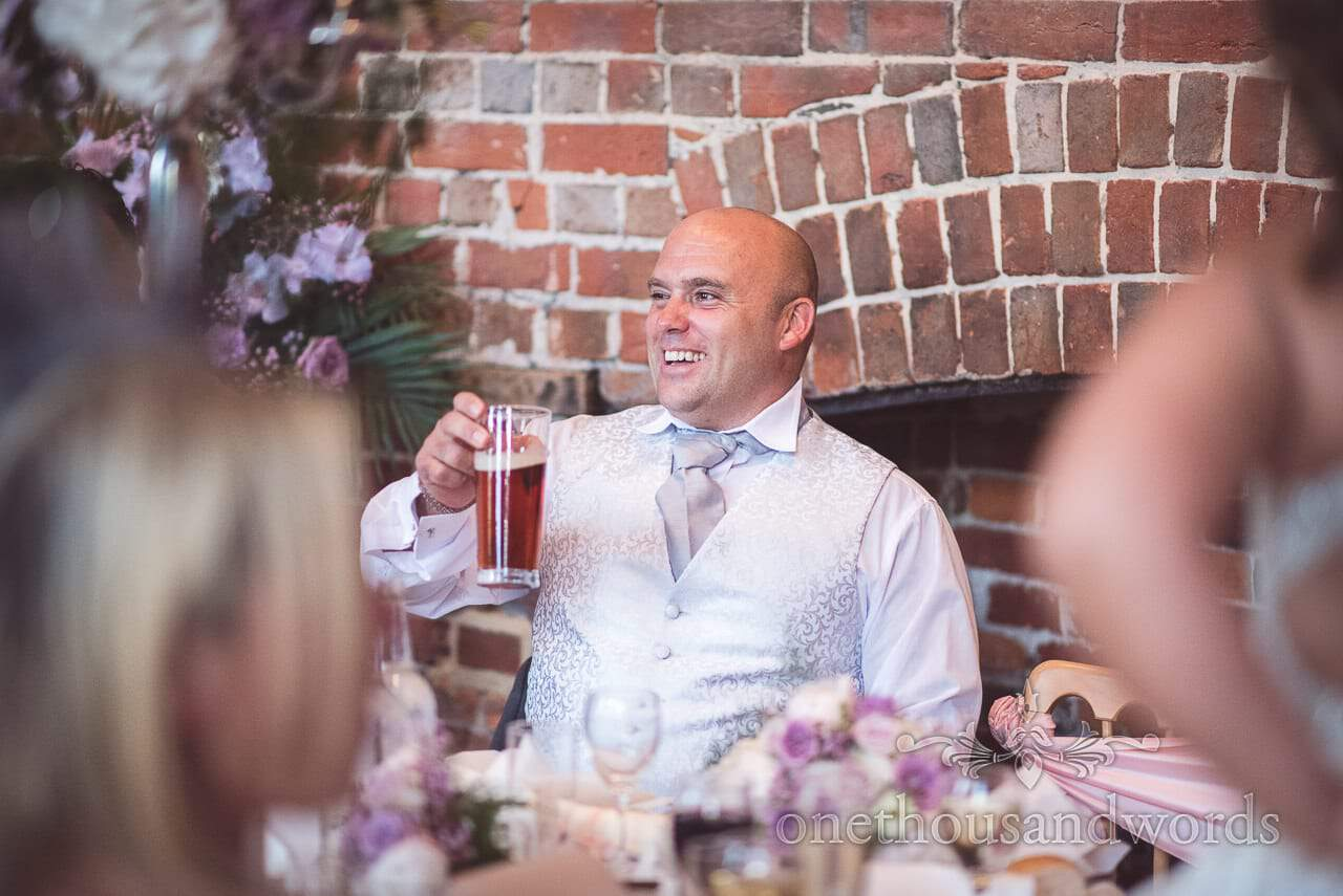 Groom raises his pint of beer during Highcliffe Castle Wedding breakfast