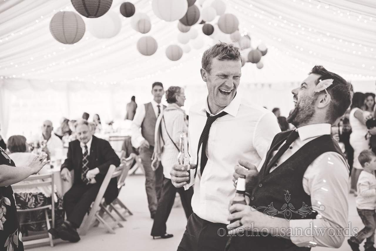 Groom shares joke with brother in law in marquee during reception