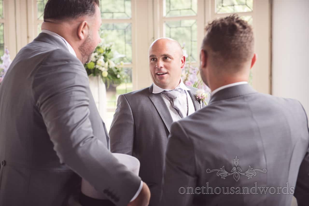 Groom talks with grooms men before Highcliffe Castle Wedding ceremony