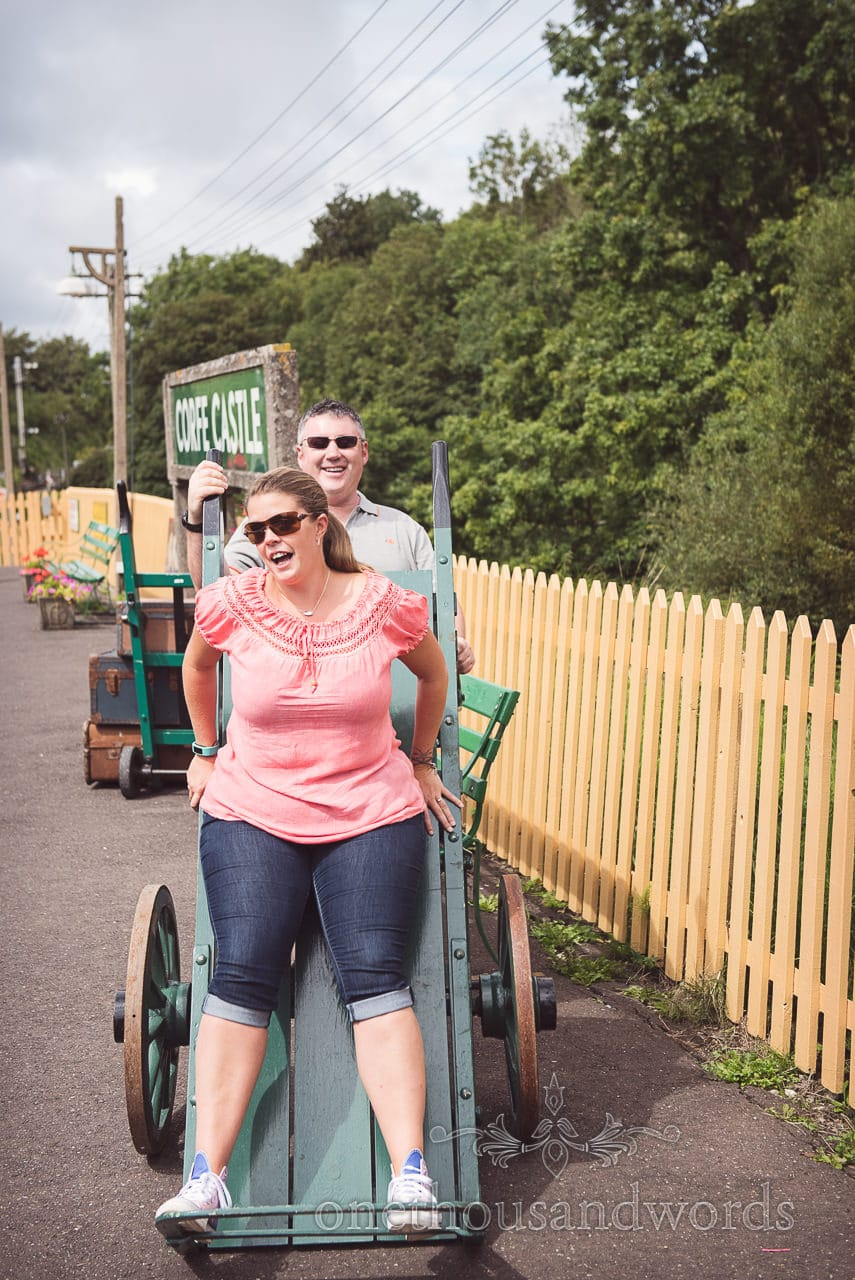 Groom to be wheels fiancée on luggage carrier at Steam Railway station