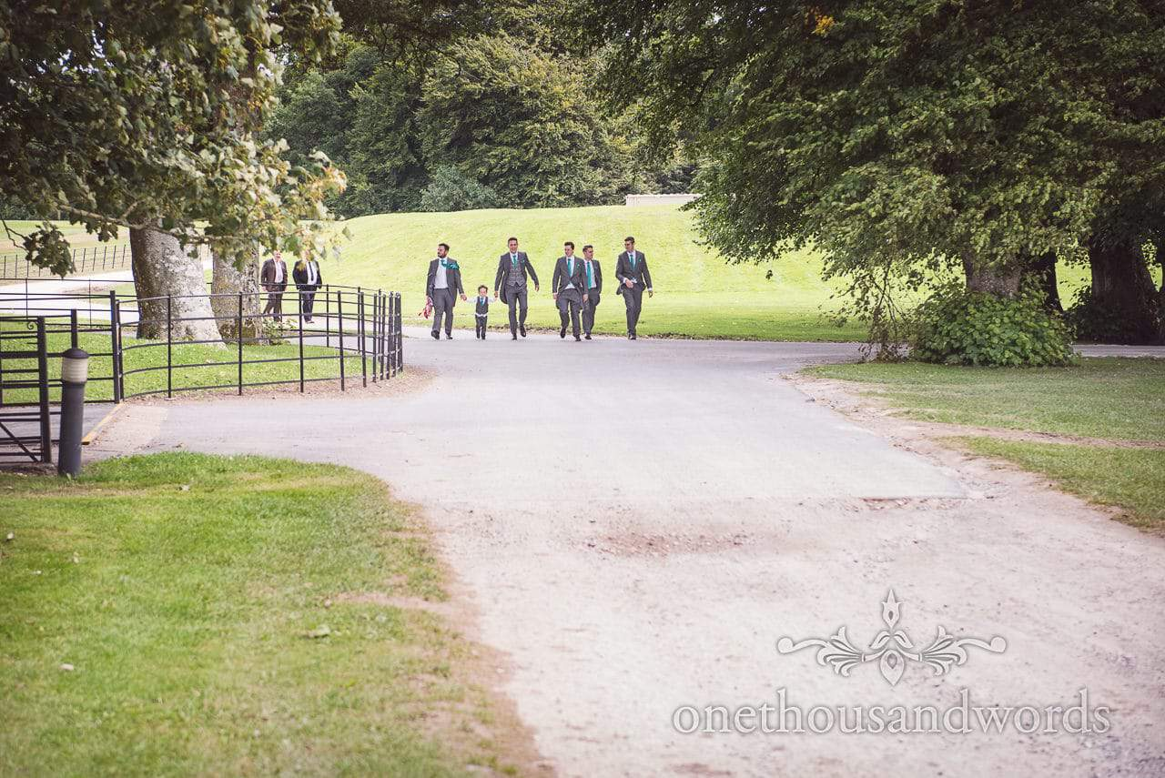 Grooms party walk up road at Lulworth Castle Wedding Photographs