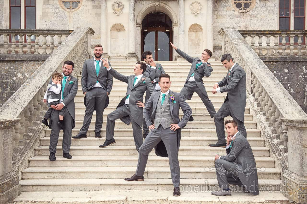 Groomsmen strike a pose on staircase at Lulworth Castle Wedding Photographs