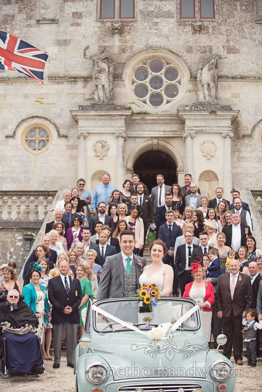 Guests and newlyweds pose for group photograph at Lulworth Castle Wedding Photographs