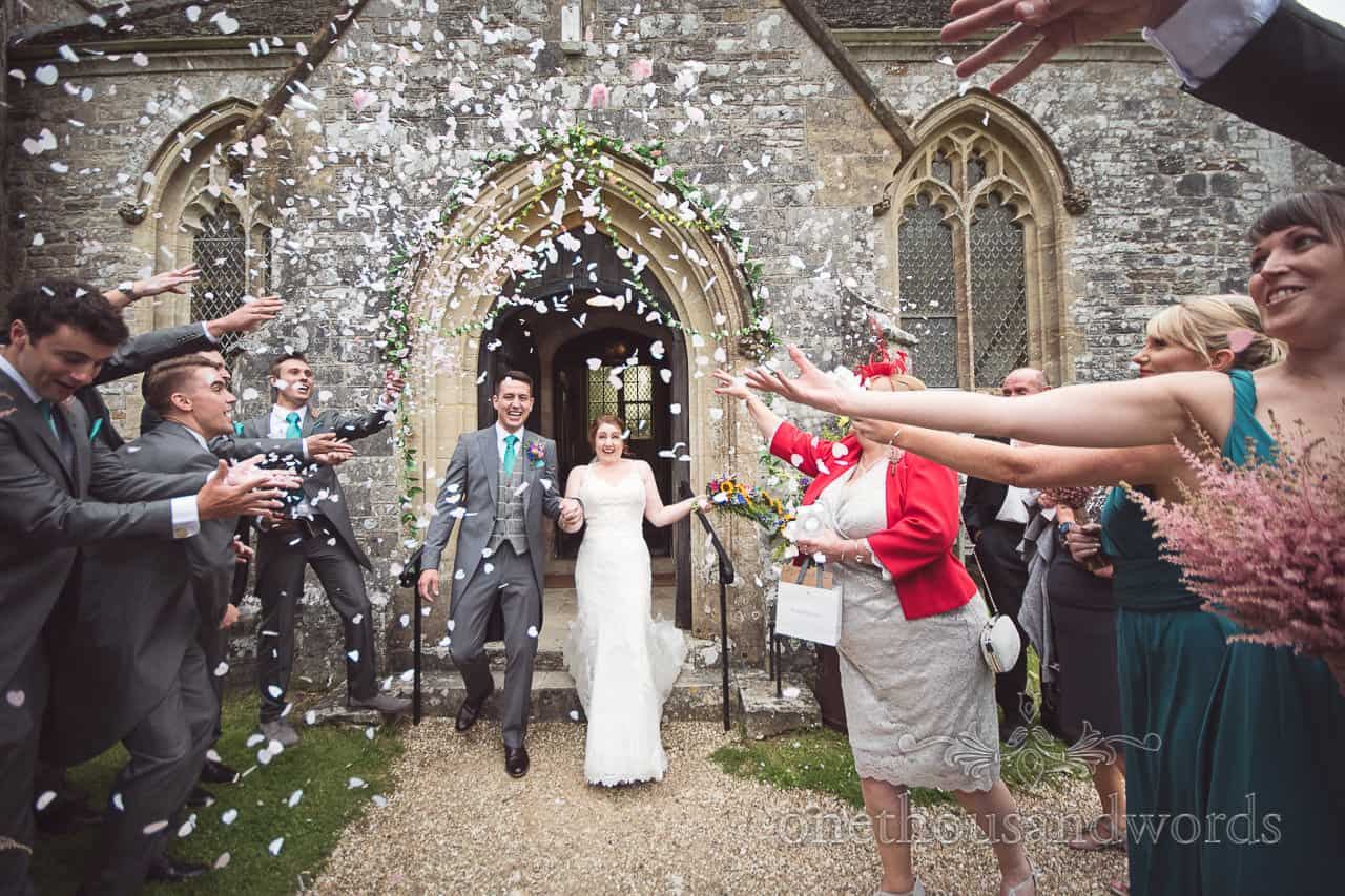 Guests shower newlyweds with confetti at Lulworth Castle Wedding Photographs