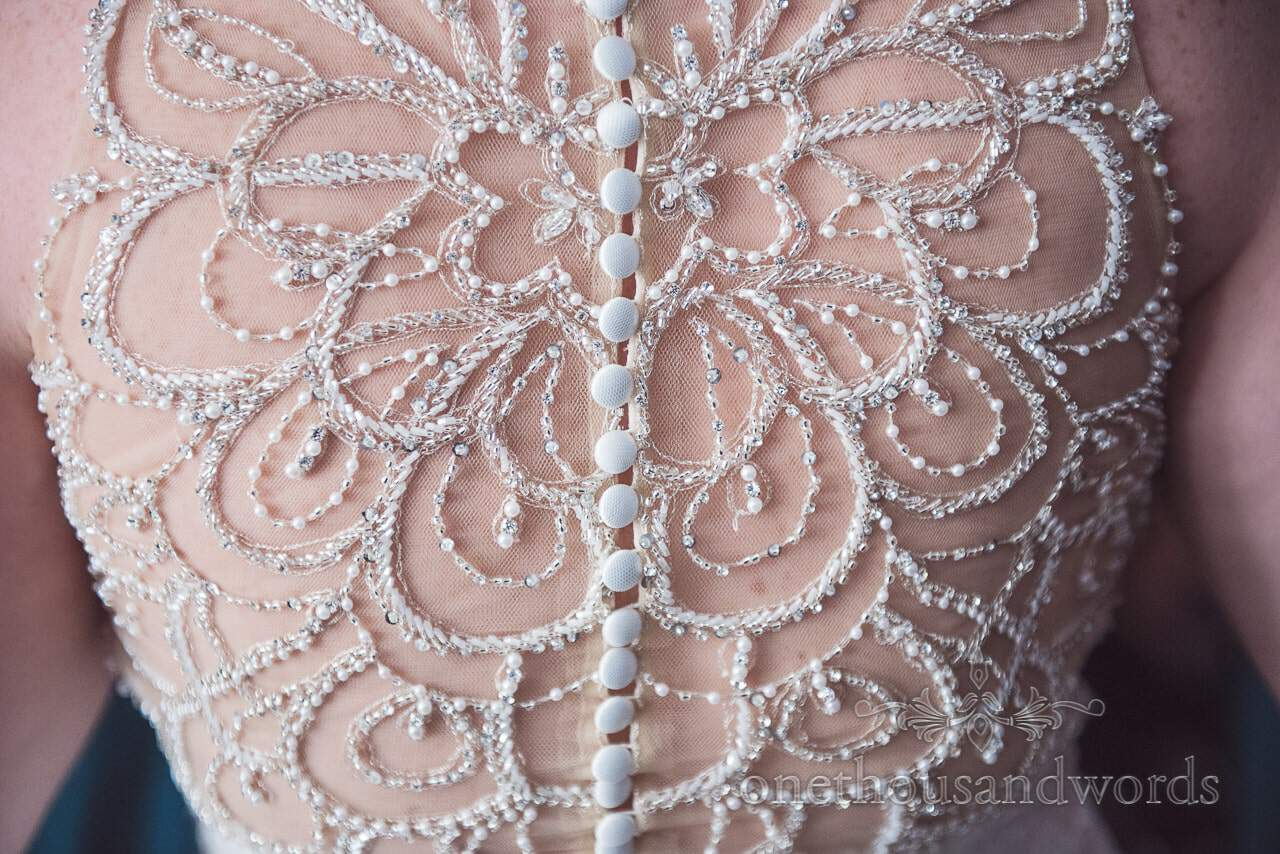Intricate detailed back of wedding dress at Lulworth castle wedding