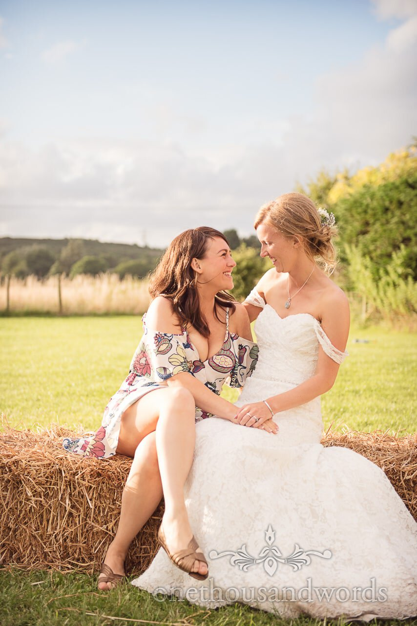 Laughing bride and friend on hay bale during garden reception