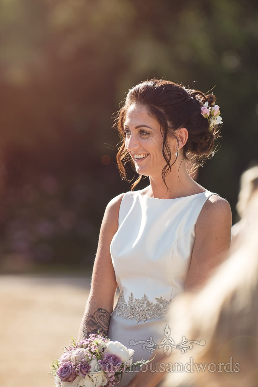 Matron of honour in sunshine at Highcliffe Castle Wedding drinks reception