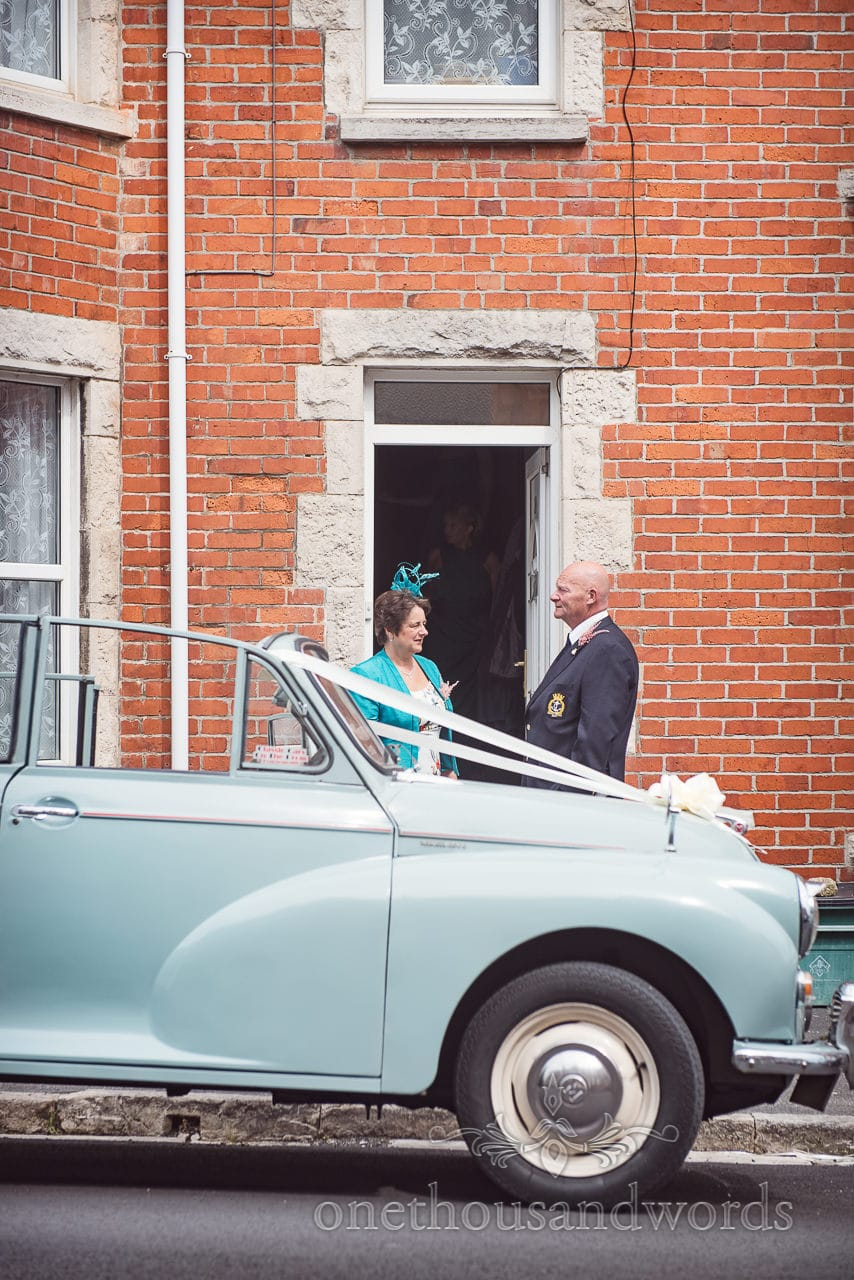 Mother and Father of the bride with Morris Minor wedding car