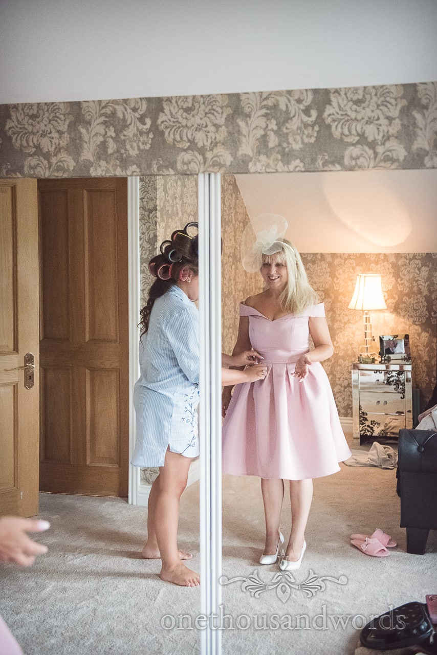 Mother of bride is helped into 1950's pink mother of bride dress on wedding morning