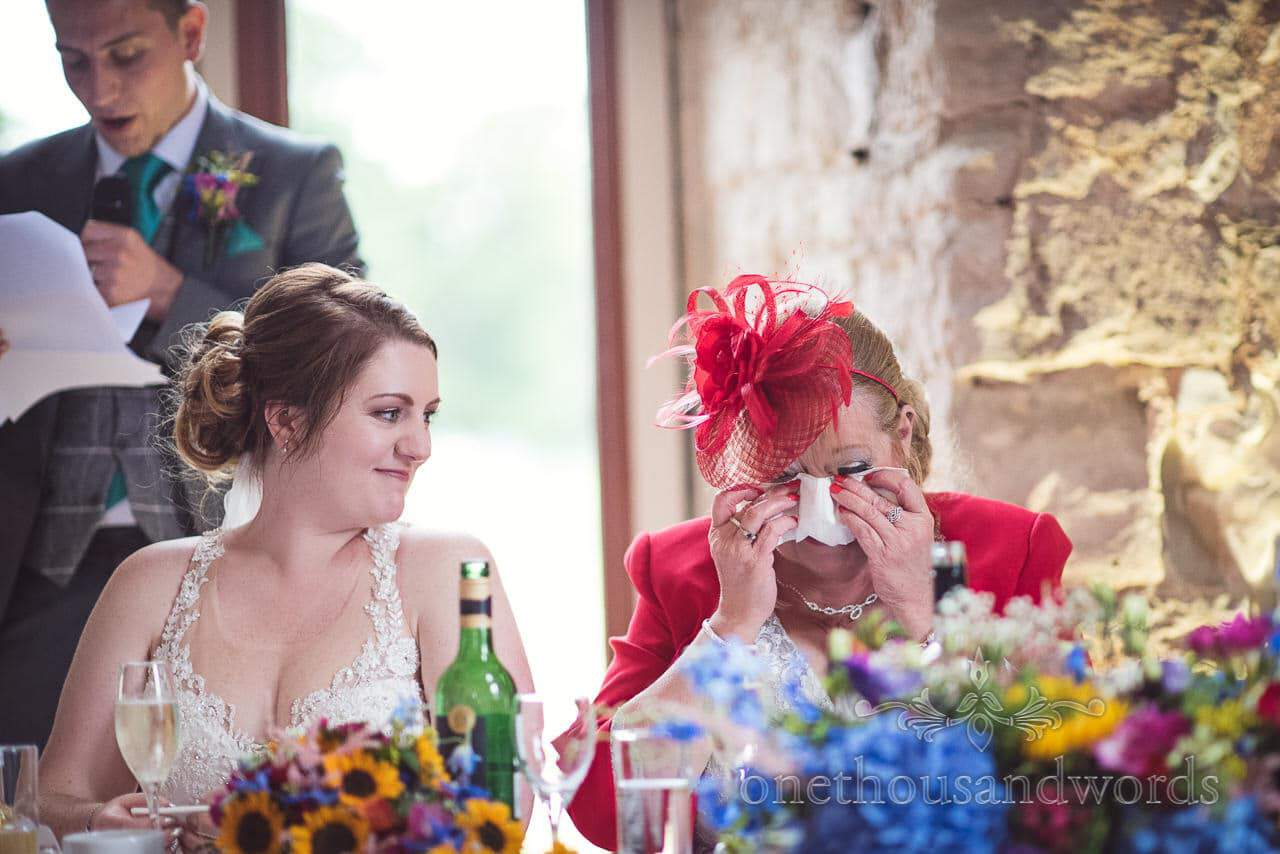 Mother of the groom wipes away tears during grooms speech at Lulworth Castle