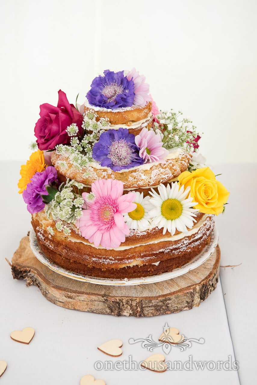 Naked Victoria Sponge Wedding Cake on wooden tree slice with colourful flowers